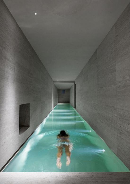 Hallenbad zu Hause Minimalismus pur längliche Form Mädchen im Wasser graue Fliesen eingebaute Beleuchtung