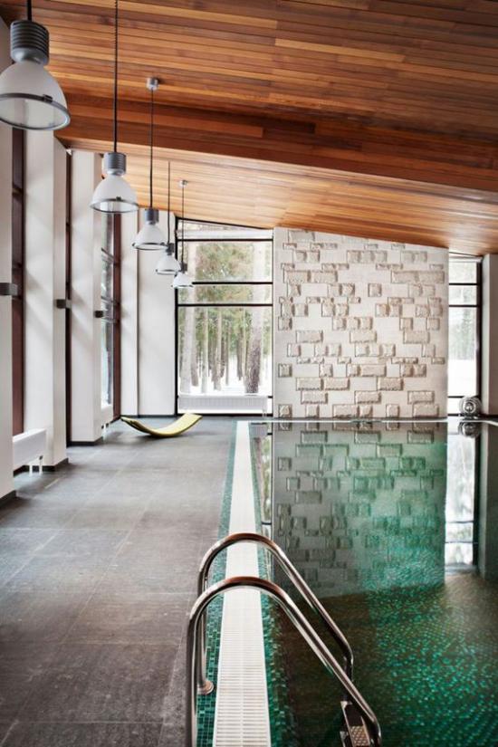 Hallenbad zu Hause interessantes Design Holzdecke gefliester Boden Ziegelwand Hängeleuchten hohe Glasfenster