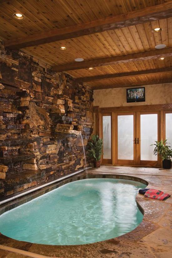 Hallenbad zu Hause rundes Spa Becken raue Steinwand Brunnen angenehme Raumatmosphäre hohe Fenster viel Licht