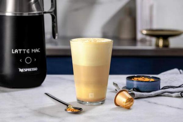 Kurkuma Kaffee in Schichten mit viel Schaum darauf Espresso Kanne daneben