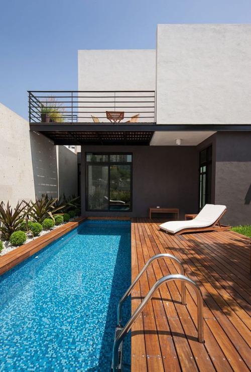 Schmale Pools auf wenig Platz für kleine Gärten Deck aus Holz Pool-Treppe aus Metall moderne Relax Liege rechts grüne Pflanzen links