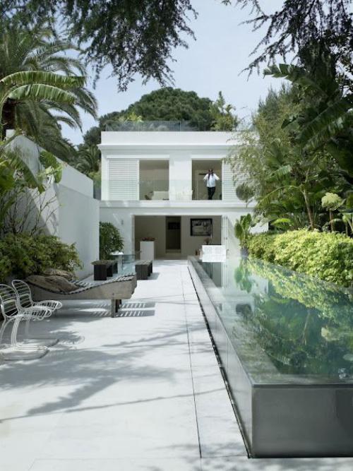 Schmale Pools auf wenig Platz für kleine Gärten Glaswände weißes Haus Betonfläche Liege Stühle viel Grün