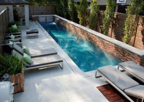 Schmale Pools auf wenig Platz für kleine Gärten Steinwand Zaun viele grüne Pflanzen Relax Liegen