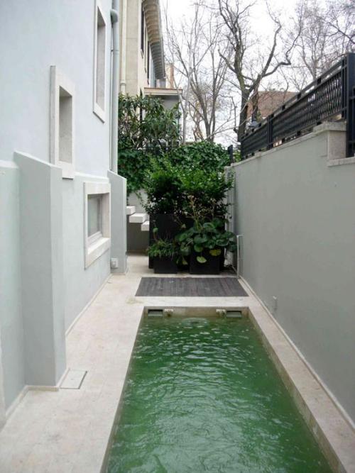 Schmale Pools auf wenig Platz für kleine Gärten begrenzte Fläche zwischen Betonzaun Hausseite grüne Sträucher im Hintergrund