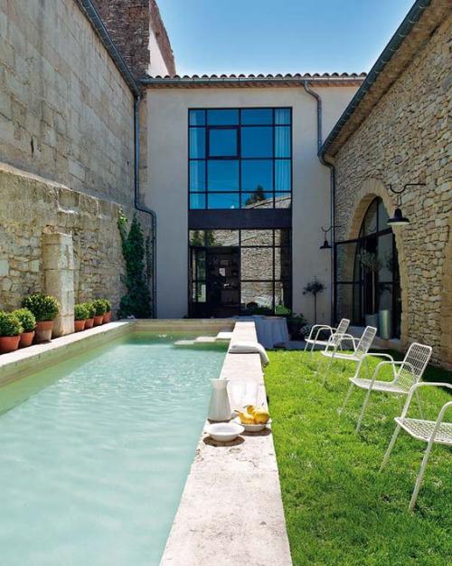 Schmale Pools auf wenig Platz für kleine Gärten exotisches Flair Steinwand links Rasen rechts leichter Zugang vom Haus Stühle