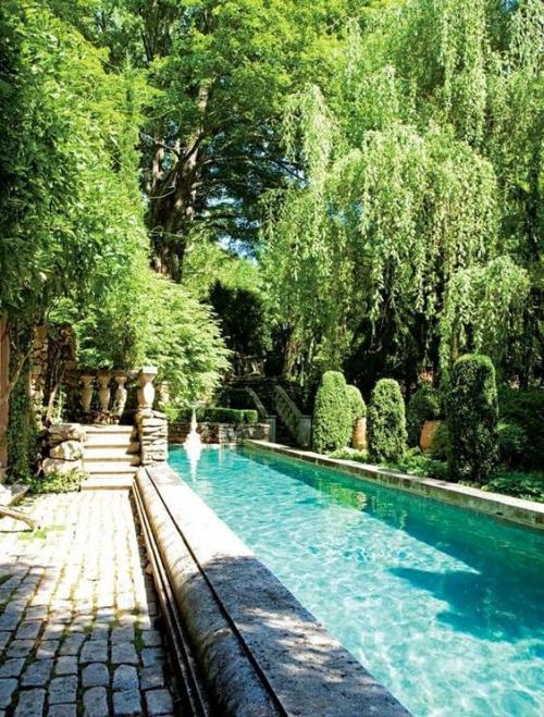 Schmale Pools auf wenig Platz für kleine Gärten viel Grün üppige Vegetation kopfsteingepflasterter Pfad links Treppe Gartenfiguren aus Stein