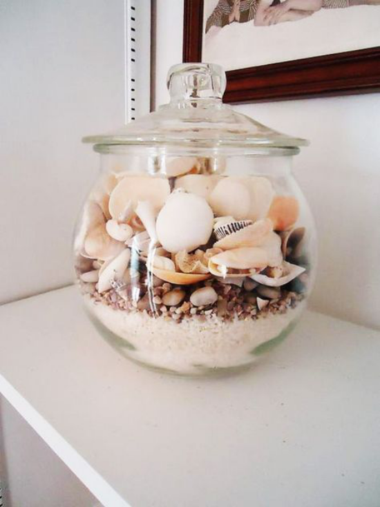 Sommerdeko mit Muscheln Glasschale mit Deckel auf der Kommode gefüllt Muscheln Sand Granulat Steine