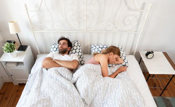 τρία σημάδια ζώδια στο κρεβάτι άντρας σε αμφιβολία γυναίκα με κινητό τηλέφωνο στο χέρι