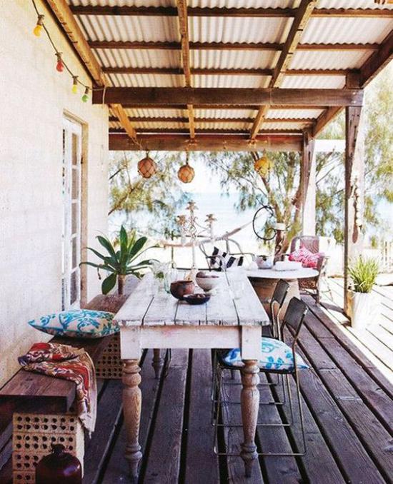 Boho Style Veranda Boden aus Holzplatten Holztisch Sitzbank aus Holz alte Metallstühle grüne Pflanzen Sitzkissen
