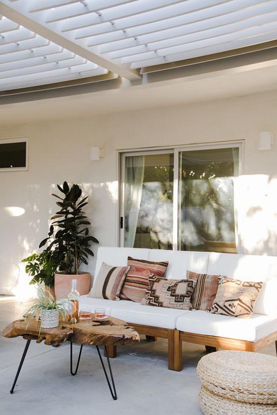 Boho Style Veranda Boho Relax-Ecke auf der überdachten Terrasse zwei Topfpflanzen