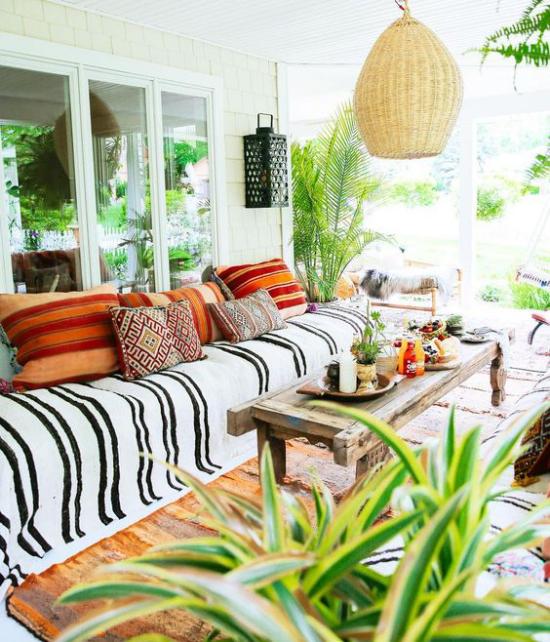 Boho Style Veranda Hängelampe aus Rattan viel üppiges Grün Deko Kissen Ethno-Muster langes Sofa