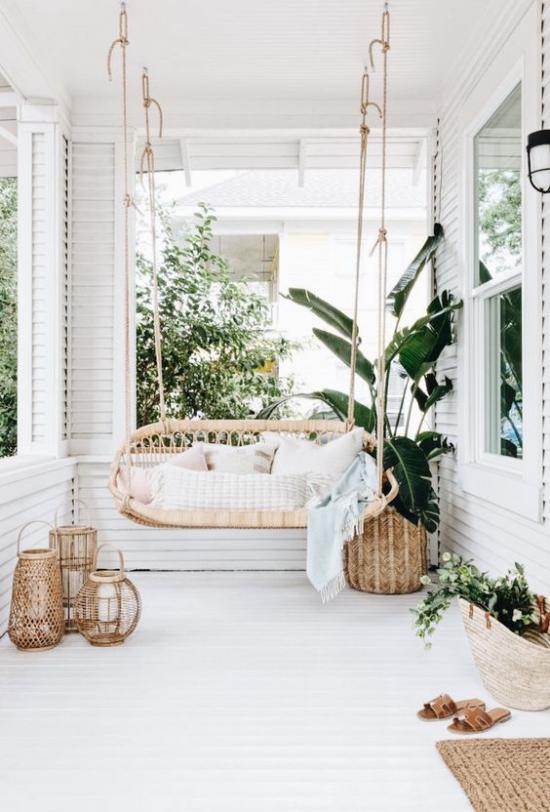 Boho Style Veranda Schaukel weiße Textilien grüne Pflanzen
