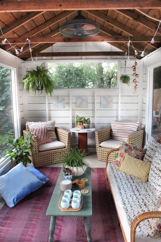 Boho Style Veranda Sessel aus Rattan Sofa rechts üppige grüne Pflanzen Deko Kissen
