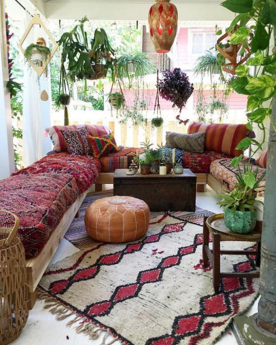 Boho Style Veranda Teppich in grauweiß und Weinrot Sofa bunte Decke viele grüne Pflanzen Hängelampe