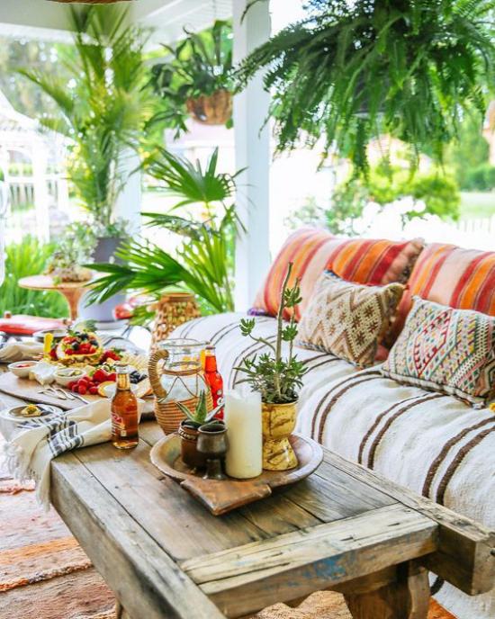 Boho Style Veranda aller Holztisch Sofa viel üppiges Grün angenehme Atmosphäre