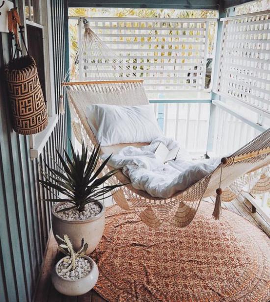 Boho Style Veranda kleine Fläche Hängematte Makramee runder Teppich zwei weiße Töpfe grüne Pflanzen