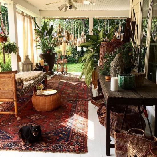 Boho Style Veranda sehr stilvoll einladend Perser Teppich in Dunkelrot viele üppige Grünpflanzen Holz Rattan Hund