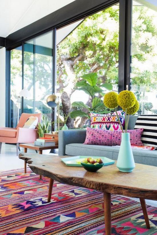 Dekoideen Wohnzimmer Ethno-Teppich viele Farben bunte Wurfkissen deckenhohes Fenster viel Natur