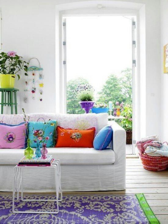 Dekoideen Wohnzimmer weißes Sofa bunte Wurfkissen geöffnete Balkontür Natur draußen