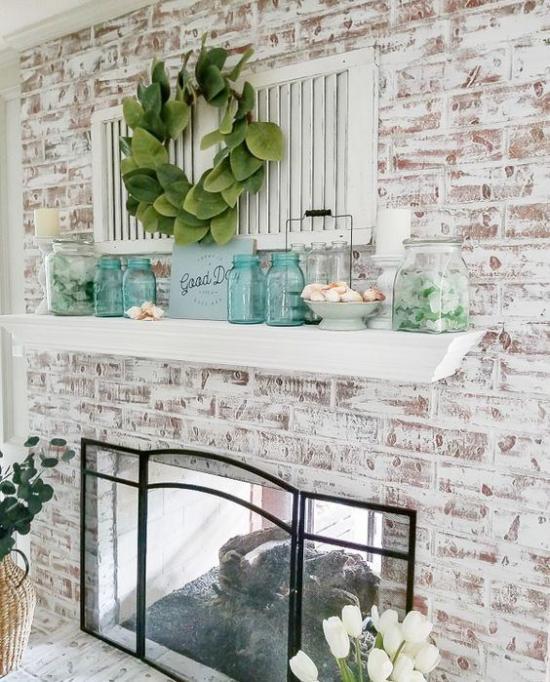 Kaminkonsole sommerlich dekorieren Ziegelwand geschmückt Glasplatte