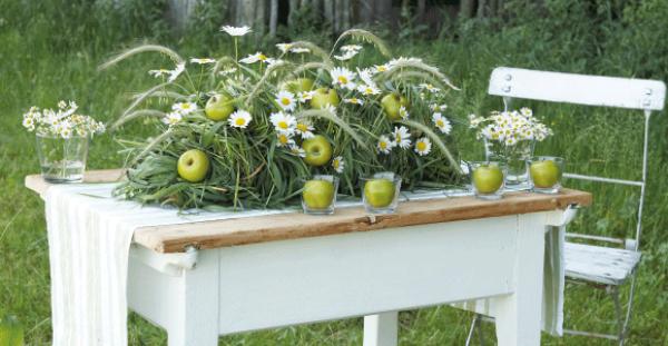 Margeriten Tischdeko draußen grüne Äpfel Gras auf einem alten Holzt