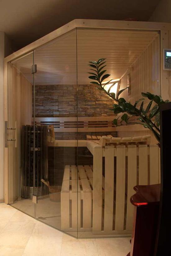 Sauna zuhause saunieren Steinwand Bänke aus Holz hinter Glaswand schickes Design