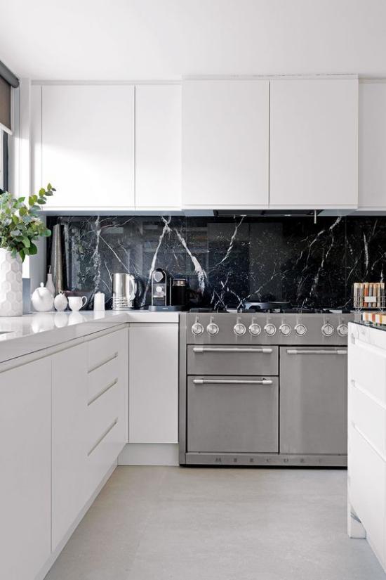Schwarzer Marmor im Interieur moderne Küche weiße Schränke schwarze Küchenrückwand aus Marmor graue Küchengeräte