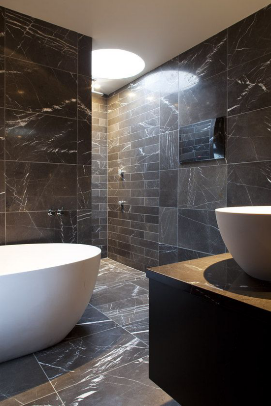 Schwarzer Marmor im Interieur schickes Badezimmer weiße Badewanne graue Marmorplatten