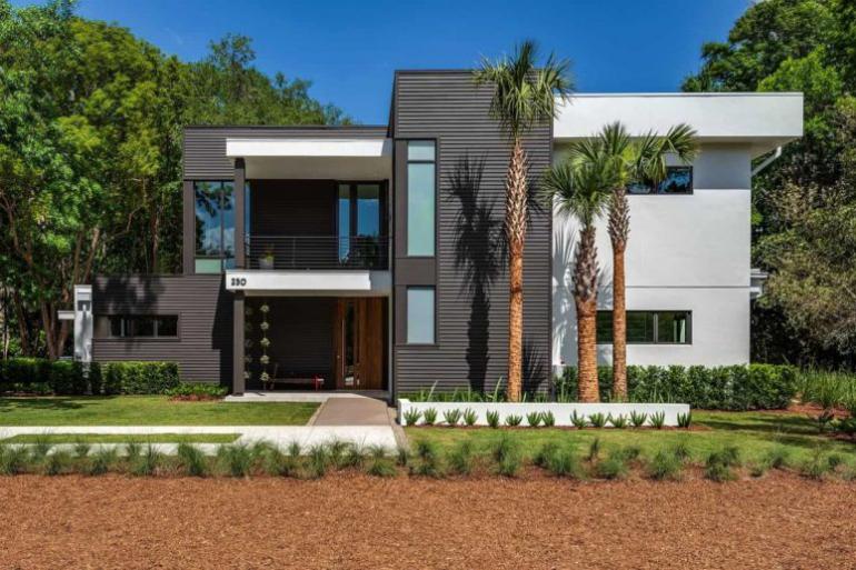 Einfamilienhaus in Florida mit offenem Wohnkonzept Aussicht von der Straße viel Grün ringsum elegante Hausfassade