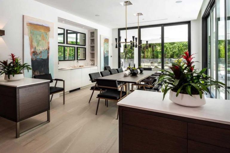 Einfamilienhaus in Florida mit offenem Wohnkonzept dunkle Möbel freundliche Raumatmosphäre zwei Topfpflanzen Übergang zur Veranda
