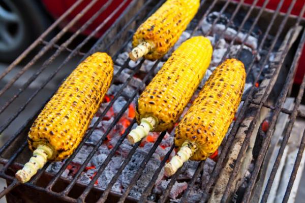 Maiskolben grillen Rost glühende Kohle Sommerparty im Freien