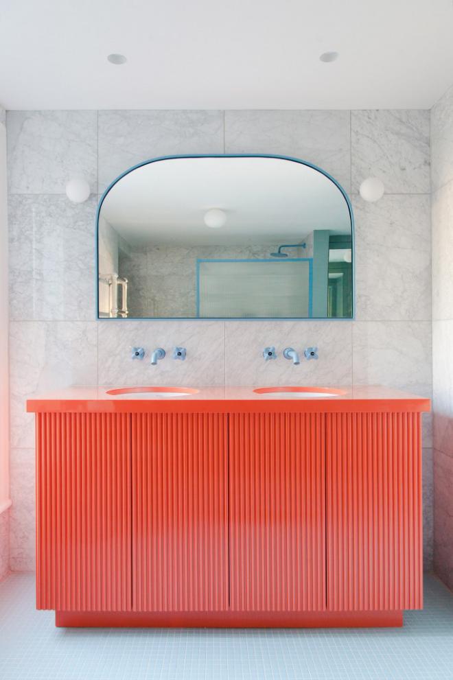 Mid-Century Modern Wohnstil Bad graue Fliesen in Marmor Optik Korallenfarbe Waschtisch großer Spiegel