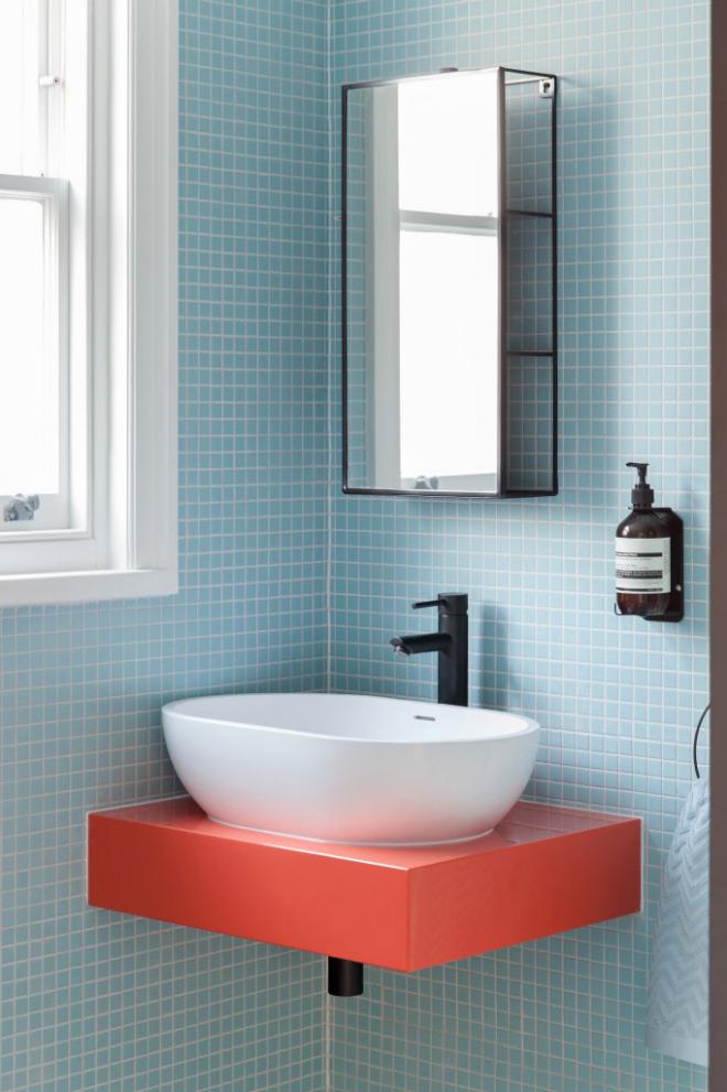Mid-Century Modern Wohnstil Gästebadezimmer die gleiche Farbpalette babyblaue Fliesen Waschtisch Korallenfarbe und Weiß
