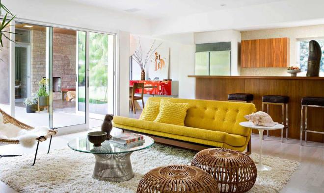Mid-Century Modern Wohnstil Wohnzimmer große Glaswand gelbes Sofa Glastisch weißer Teppich Korbsessel