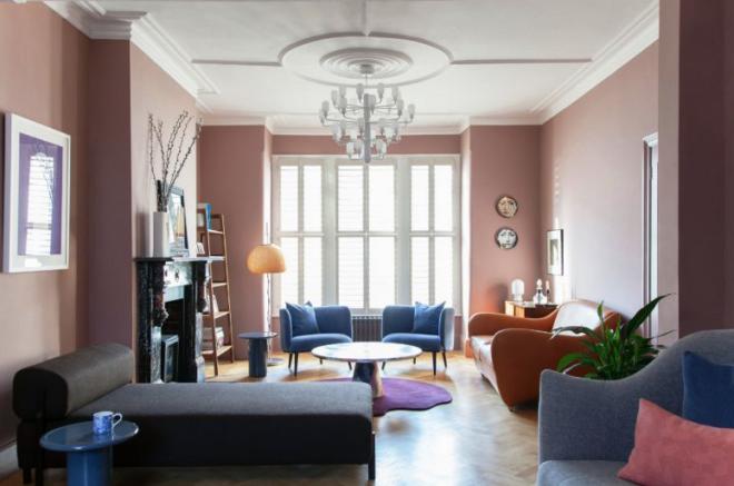 Mid-Century Modern Wohnstil Wohnzimmer rosafarbene Wände bequeme Möbel Kamin aus Stein violetter Teppich