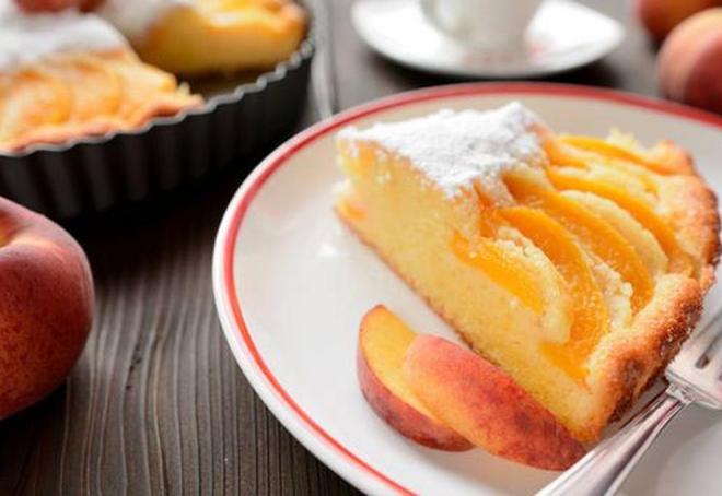 Pfirsichkuchen zubereiten zwei Rezepte klassisch und vegan ein Stück mit Zucker bestreut im Teller serviert