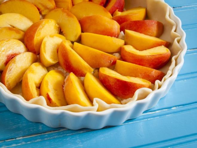 Pfirsichkuchen zubereiten zwei Rezepte klassisch und vegan mit frischen Pfirsichen in Scheiben geschnitten belegt