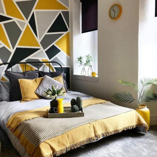 Schlafzimmer Ideen in Grau und Gelb Akzentwand hinter dem Schlafbett gemustert in geometrischen Figuren