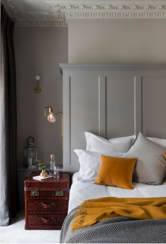 Schlafzimmer Ideen in Grau und Gelb einfache Raumeinrichtung alte Koffer als Nachttisch weiße Bettwäsche graue Decke gelbes Kissen