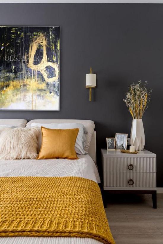 Schlafzimmer Ideen in Grau und Gelb graphitgraue Wand dunkler Hintergrund Wandbild gelb gestrickte Bettdecke