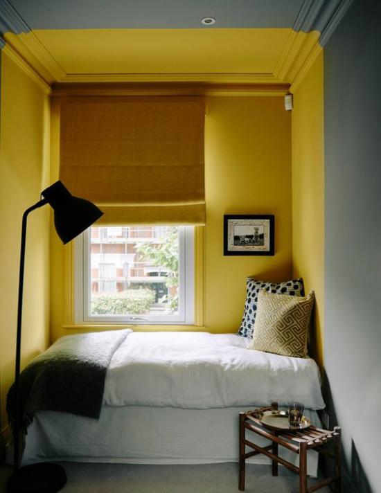 Schlafzimmer Ideen in Grau und Gelb kleines Zimmer Bett vor dem Fenster gelbe Wand gelbe Rollos weiße Bettwäsche