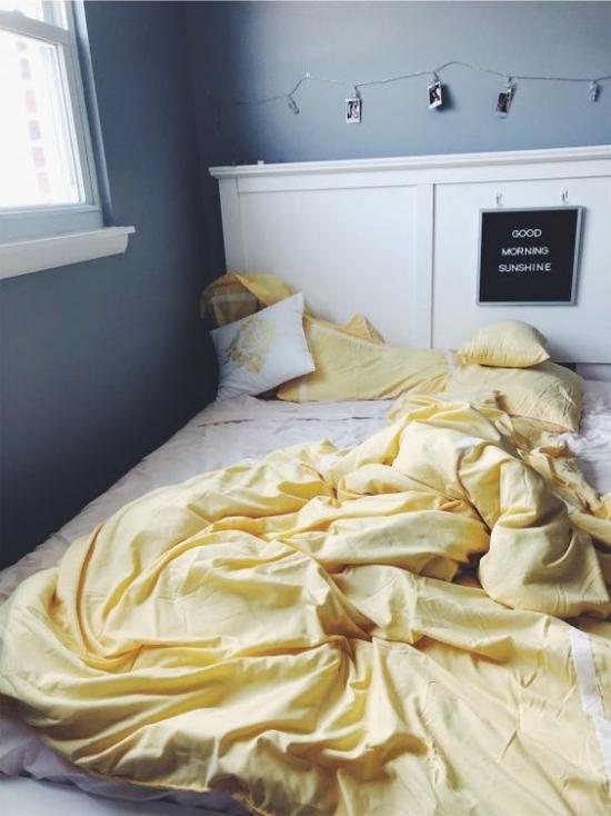 Schlafzimmer Ideen in Grau und Gelb ungemachtes Bett weiße Bettwäsche hellgelbe Decke dunkelgraue Wände Fenster