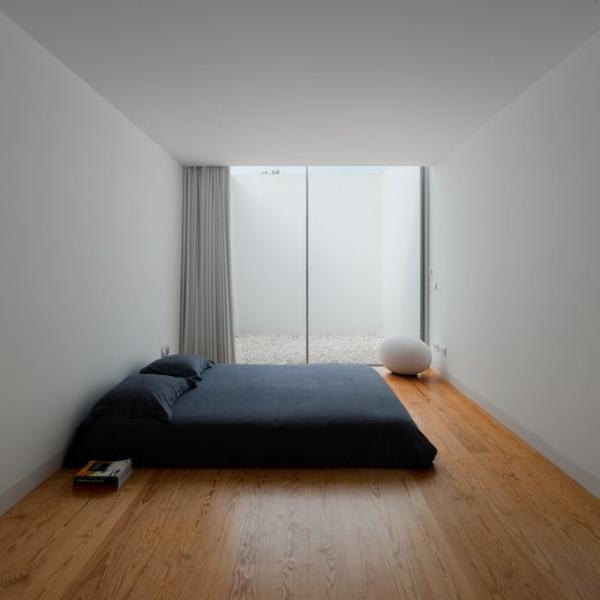 Schlafzimmer minimalistisch einrichten großes Deckenhohes Fenster graue Wände schwarzes Schlafbett Boden aus hellem Holz