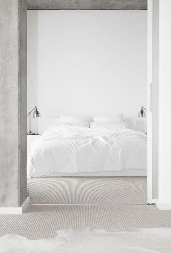 Schlafzimmer minimalistisch einrichten weiße Bettwäsche Betonwand im Vordergrund Türrahmen