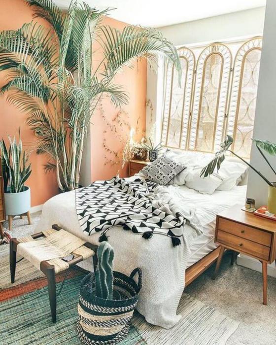 kleines Schlafzimmer Boho Stil Bett aus Holz Holzboden Korb viele grüne Pflanzen