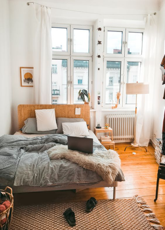 kleines Schlafzimmer Holzboden Bett aus Holz beige Bettdecke großes Fenster