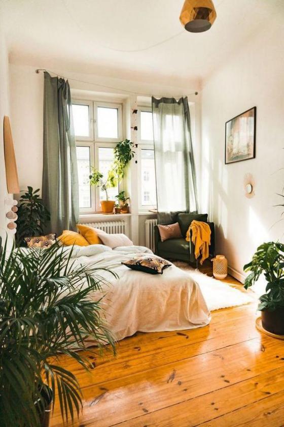 kleines Schlafzimmer Holzboden viele grüne Pflanzen Bett in Grün gebettet Sessel in der Ecke neben dem Fenster Akzente in Gelb