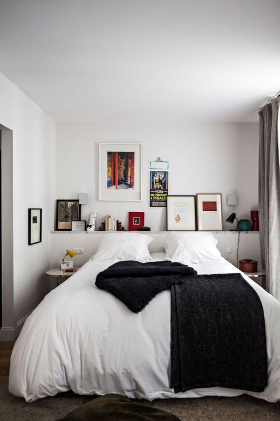 kleines Schlafzimmer einfaches Interieur Schlafbett weiße Bettwäsche Regal Akzente in Schwarz Kontrast