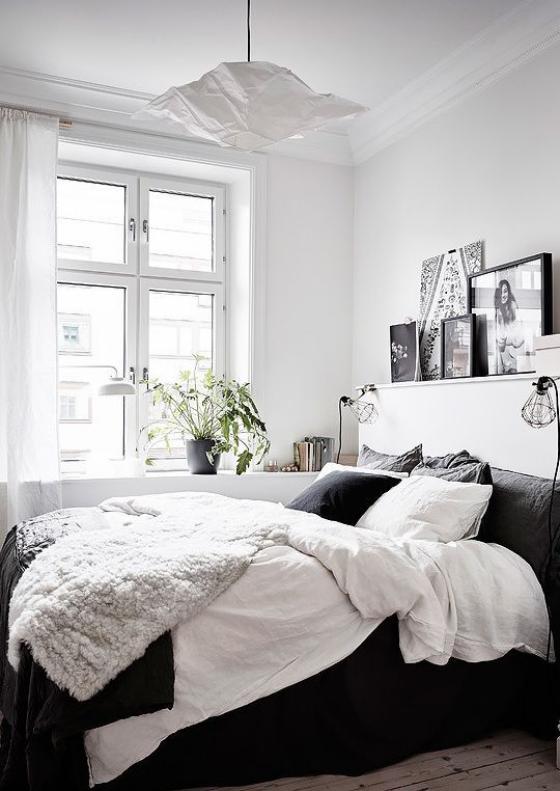 kleines Schlafzimmer einfaches Raumdesign bequemes Bett visueller Kontrast zwischen Weiß und Schwarz