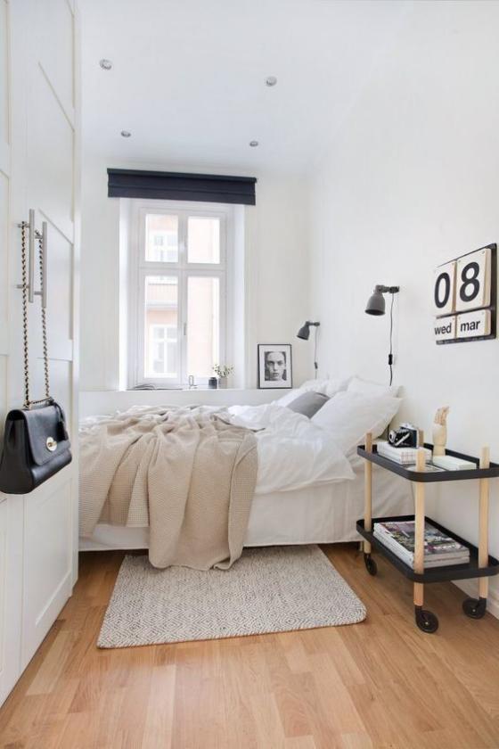kleines Schlafzimmer einfaches skandinavisches Design Weiß dominiert Tisch auf Rollen Kalender an der Wand